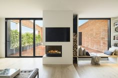 Modern home with living room, medium hardwood floor, wall lighting, bench, and two-sided fireplace. Photo 2 of Black to Light