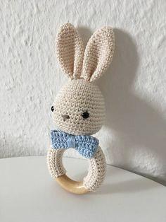 Un crochet lapin hochet/jouet en crème et bleu de bébé. L'anneau a un diamètre extérieur de 65 mm et 12mm d'épaisseur. La laine utilisée est certifiée Oeko Tex 100 et correspond à la classe product I. L'anneau en bois est la salive, standard et exempt de substances nocives et donc