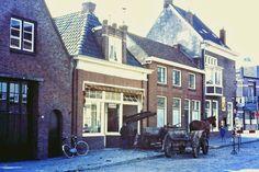 1969. Verbouwing bakkerswinkel de Vries, Keppelstraat westzijde. Nu is bakkerij A. J. van der Bijl hier gevestigd. Deze foto laat nu een stukje van de van de oude tijd zien. Toen was dit nog niet ongewoon. Die originele houten karren, dat geduldig wachtende paard en die Jacobsladder door het raam. Prachtig toch? Dit soort beelden krijgt u in het echt waarschijnlijk niet meer te zien in Dokkum.