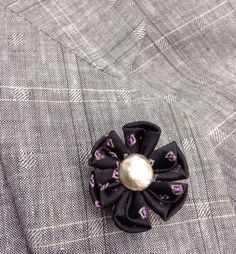 An elegant black lapel flower made in the Japanese tsumami kanzashi style for modern guys! I used a black silk with tiny bits of gray and purple to make this flower, and added a gray coin pearl to the center. I mounted everything onto a tie tack finding with a clutch back. Complements suits, blazers, sport jackets, hats, cardigans and more.   Kanzashi flowers are made from folded fabric squares, one petal at a time. Originally, apprentice geisha made kanzashi hair accessories from their old…