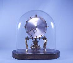 Relógio de mesa KUNDO Kieninger & Obergfell - corda para 1 ano - Alemanha, com cúpula em vidro ovalada e base em metal. Revisado e funcionando. Base medindo 23 cm x 12 cm / Altura 25 cm.