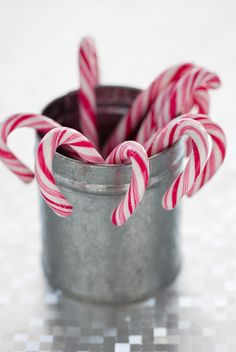 Candy canes hung from zinc planters with greenery would be beautiful.