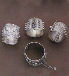 Ethiopia & Yemen | Silver, and glass bracelets | Early 20th Century | Decorated with projections that deflect the evil eye, these cuffs are also found at Harar in Ethiopia. Their filigree and granulation work, influenced by techniques and styles from Arabia and the East, is the finest among the world.