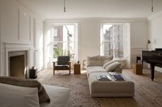 William Smalley flat in Bloomsbury, silver bottom light bulb pendants, wood floors with kilim, white paneled walls   Remodelista