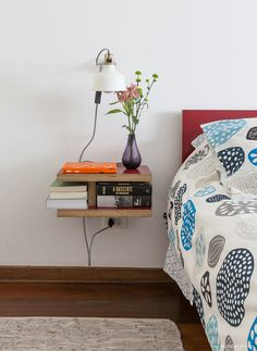 Cabeceira de madeira revestida com fórmica vermelha, roupa de cama estampada e criado mudo enxuto.