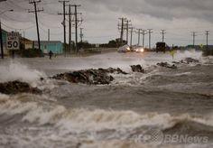 米東部ノースカロライナ(North Carolina)州ナグスヘッド(Nags Head)で、ハリケーン「アーサー(Arthur)」の接近による強風と高波にされされる国道64号線(2014年7月3日撮影)。(c)AFP/Getty Images/Mark Wilson ▼4Jul2014AFP|ハリケーン「アーサー」、米東海岸沿いを北上 http://www.afpbb.com/articles/-/3019678