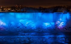 Ice and water flow over the illuminated American Falls, viewed from the Canadian side in Niagara Falls, Ontario, Canada, on January 2, 2018.