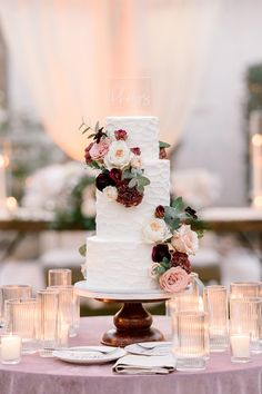 """From the editorial """"How to Transform a Moody Color Palette With Soft Floral Designs."""" This white wedding cake adorned with blush and burgundy florals went perfectly with this couple's moody, yet romantic wedding theme!  LBB Photographer: @scottanddanaphotographers Cake: @aboveandbeyondcakeseg  #weddingcake #whiteweddingcake #cakeinspiration #moodyweddingcake #flowerweddingcake"""