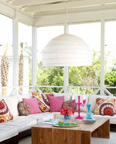 Cozy, modern, and bright! A large paper chandelier comes to life as the room's focal point, while a simple color palette of neutral tones and warm accent hues brightens the space. Basically, what we're saying is... we love this porch!