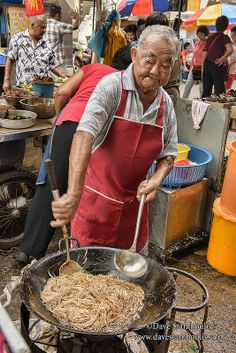 Cooking stir fried noodles in a wok in Penang, Malaysia