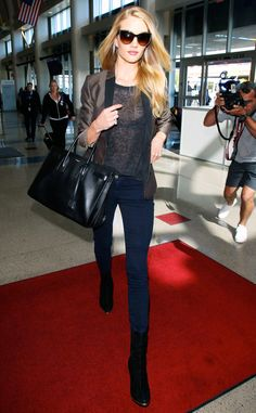 Rosie Huntington-Whiteley walks through the airport like it's a catwalk in her sheer top, jacket, and super skinny jeans.