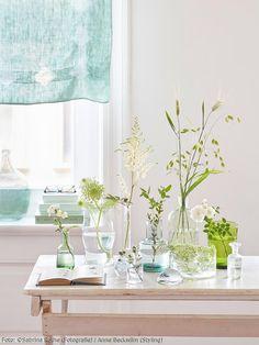 Glasvasen mit zarten Zweigen und Blüten sind eine tolle Deko-Idee! Mehr Inspiration und Bilder zu unserem Wohnbuch des Monats gibt es auf roomido.com #roomido #blumen #grün #dekoration #glas
