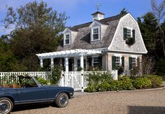 Browse the exterior and interior images of Rural Vineyard located in historic Edgartown, Martha's Vineyard. The property includes the main home, an attached carriage house, and extensive outdoor living spaces including a pool area and pool cabana.