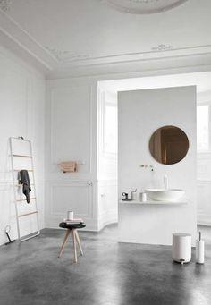 joli salon blanc avec sol en beton ciré gris et moulures decoratives et corniche plafond