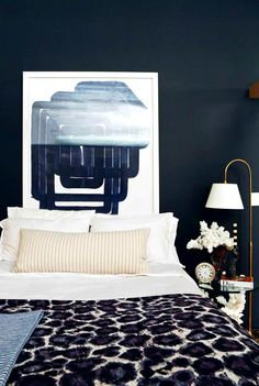 Black walled bedroom with bold artwork, cheetah print bedspread and gold floor lamp