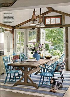 Mixed coloured chairs in contrast with wood... Love that table and the dog too!