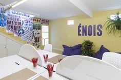 Decora Rosenbaum Temporada 1 - ÉNois. Decoração amarela, ilha de mesas de escritório, lambe lambe. Foto: Felipe Felco Valle