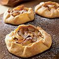 Elegant and flavorful, these individually sized pies will impress guests with their orange zest–flecked crust encasing thin slices of apples sprinkled with almonds, nutmeg-sugar mix and orange juice.
