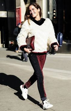 Gala Gonzalez wears a fur sweatshirt, suede red and black pants, white sneakers, and a burgundy clutch