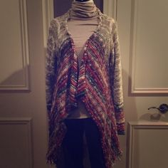 Multi colored open cardigan Woven knit cardigan with beige and white then flows into a multi stripe of reds, oranges and greens. Long sleeve and open. EUC BKE Sweaters Cardigans