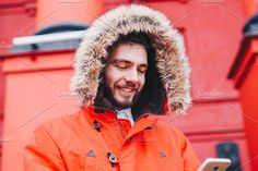 handsome young male student with a toothy smile and a beard stands on a red wall background in a bright red winter jacket with a hood with fur in winter. Uses a mobile phone, talk and call , Restaurant Website Templates, Red Walls, Canada Goose Jackets, Georgia, Handsome, Winter Jackets, Fur, Student, Bright