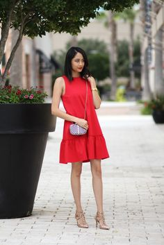 Lily of Daily Craving is bold and bright in our red ruffle dress. She styles it with a small crossbody bag studded heels for a colorful street style look | Banana Republic