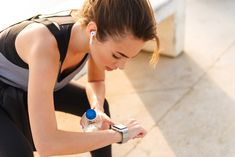 Picture of young sports woman sitting outdoors listening music with earphones looking at watch. - Benefits in Wearable Technology Mind Blowing Facts, Walking Exercise, Wearable Technology, News Health, Regular Exercise, Medical Care, Intermittent Fasting, Physical Fitness, Get In Shape