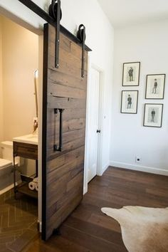 Although slightly unconventional, this sliding barn door in reclaimed wood is a fun and offbeat means of introducing a new bathroom renovation brought to you by Pure Design Interiors! The door makes a strong statement in its hardware, dark color and rolling closure, yet radiates a whimsical charm nonetheless.