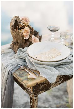 Aged wood table with centerpiece of blush roses and natural wood and a place setting of white china on hand dyed silk with place card of natural paper and white calligraphy. Styling and florals by Janna Brown Design Co., silk by Silk & Willow, calligraphy by Linen & Leaf. Image by Sleepy Fox Photography.