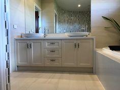 Traditional vanity completed in Polytec Ballarat profiled doors 2-PAC painted. Quantum quartz Carrara quartz stone benchtops and bath hob.