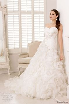 Long white strapless wedding dress with intricate skirt ruffles from Divina Sposa.
