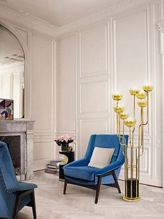 A mid century living room with blue velvet armchairs, a brass and marble floor lamp and a small black side table. Elegant living room furniture pieces that create a unique and special set by BRABBU Get inspired here: http://www.brabbu.com/en/inspiration.php