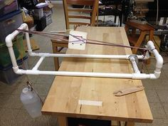 A simple pipe loom for tablet weaving. Uses a water-filled jug for tensioning. Cheap, easy to build, and works great.  http://www.weaverly.typepad.com