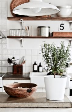 white kitchen + wood shelving + concrete counter + vintage pendant
