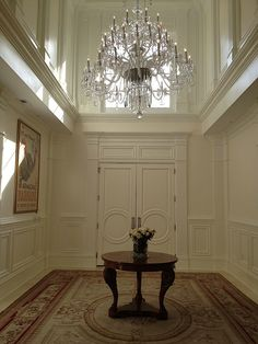 Grand entryway with chandelier in one of our custom Mediterranean style homes.