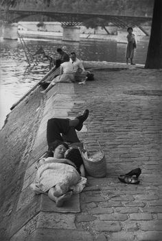 Paris-plage existait déjà... / Lovers by the Seine. / Paris, France. / By Henri Cartier-Bresson, 1955.