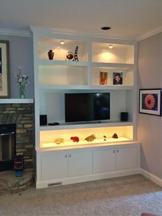 Contemporary entertainment center with illuminated glass shelf display area.  Design by Brian Thomas.