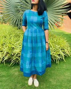 Shop online Shades of blue checks dress The shades of blue checks cotton dress is a pretty dress perfect for this summer season! the dress is made in pure cotton fabric and is adorned with red buttons at the back Long Dress Design, Dress Neck Designs, Designs For Dresses, Kalamkari Dresses, Ikkat Dresses, Frock Fashion, Fashion Dresses, Indian Designer Outfits, Designer Dresses