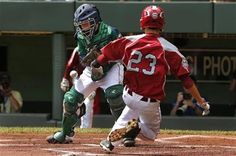 Lynnwood's Colton Walsh (23) scores as the ball gets away from Rapid City catcher Mason Litz during the first inning of a baseball game, LLWS August 16, 2014