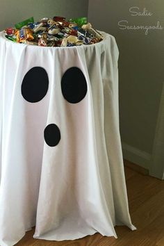 Your guests will love picking out a piece (or two or three!) of their favorite candy from this ghostly bucket. Get the tutorial at Sandie Seasongoods. What you'll need: Black felt ($6; amazon.com); White spray paint ($4; amazon.com); Candy bowl ($8; amazon.com); White fabric ($9; amazon.com); bucket stand ($20; amazon.com)
