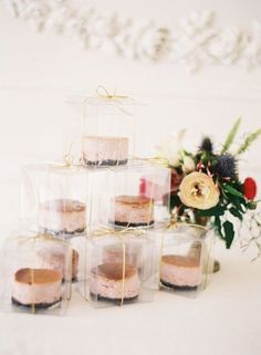 summer wedding favors in a clear container with gold bow.