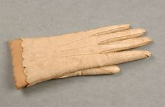 A ladies' kid leather glove, circa 1800 - 20, with three rows of pointing, scalloped slightly pinked cuff, two pearlised buttons to fasten, enlarged button holes, 20 cm long.