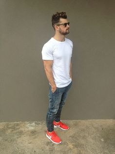 For an everyday outfit that is full of character and personality team a white crew-neck t-shirt with grey jeans. Mix things up by wearing red running shoes.   Shop this look on Lookastic: https://lookastic.com/men/looks/white-crew-neck-t-shirt-grey-jeans-red-athletic-shoes-black-sunglasses/10400   — Black Sunglasses  — White Crew-neck T-shirt  — Grey Jeans  — Red Athletic Shoes