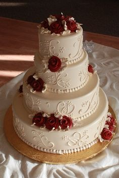 Wedding Cake: Ivory frosting and designs with red buttercream roses.