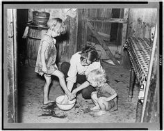 1938 | Mother washing feet and cleaning up daughters in sharecropper's shack. Southeast Missouri Farms