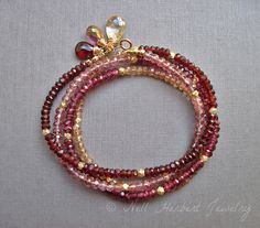 This gemstone wrap bracelet features deep red garnet, rhodolite garnet, pink quartz and champagne quartz gemstones, with interspersed gold vermeil beads. The total length is 27 inches, which wraps four times on most wrists. The bracelet is finished with a 3/4 extender chain, making it adjustable to a variety of wrist sizes. The clasp is accented with a cluster of matching wire wrapped gemstones.  This piece also works great as a long necklace.  The beads measure 3-4mm each, and the total...