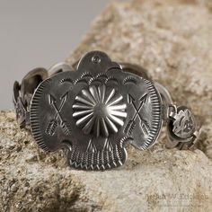 This is a really unusual Navajo bracelet from the 1930's. It has a large Thunderbird with stamped crossed arrows and stamped feathers on the tail and ten oval raised links, each stamped with a small t