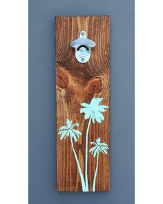 Who doesn't love drinking a beer on the beach under the shade of palm trees? Here we have a sturdy, and practical bottle opener with a trio of palm trees on the front. Made of solid hard wood, this bottle opener mounts to your wall and makes a great piece for your kitchen, bar area, or pool deck. Makes a great unique gift for any craft beer lover. Comes fully assembled with screws, so all you need to do is screw it to your wall with a beer ready in hand. Cheers! Wood is stained and ...