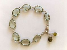 Eight wonderful pale green Garnets are faceted, irregular oval shaped and encased in sterling silver. They link together to form a charming bracelet. Two little green Garnet dangles are at the end of the extender chain, making this bracelet adjustable 7 1/2 to 8. * Garnet is said to inspire love and bring luck. It is energizing and protective. Garnet opens the heart, bestows self-confidence, and removes inhibition and taboos. When worn with other stones, garnet amplifies their effect. ...