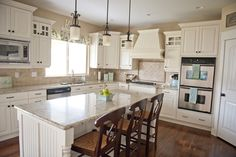 Off white cabinets with neutral granite and backsplash